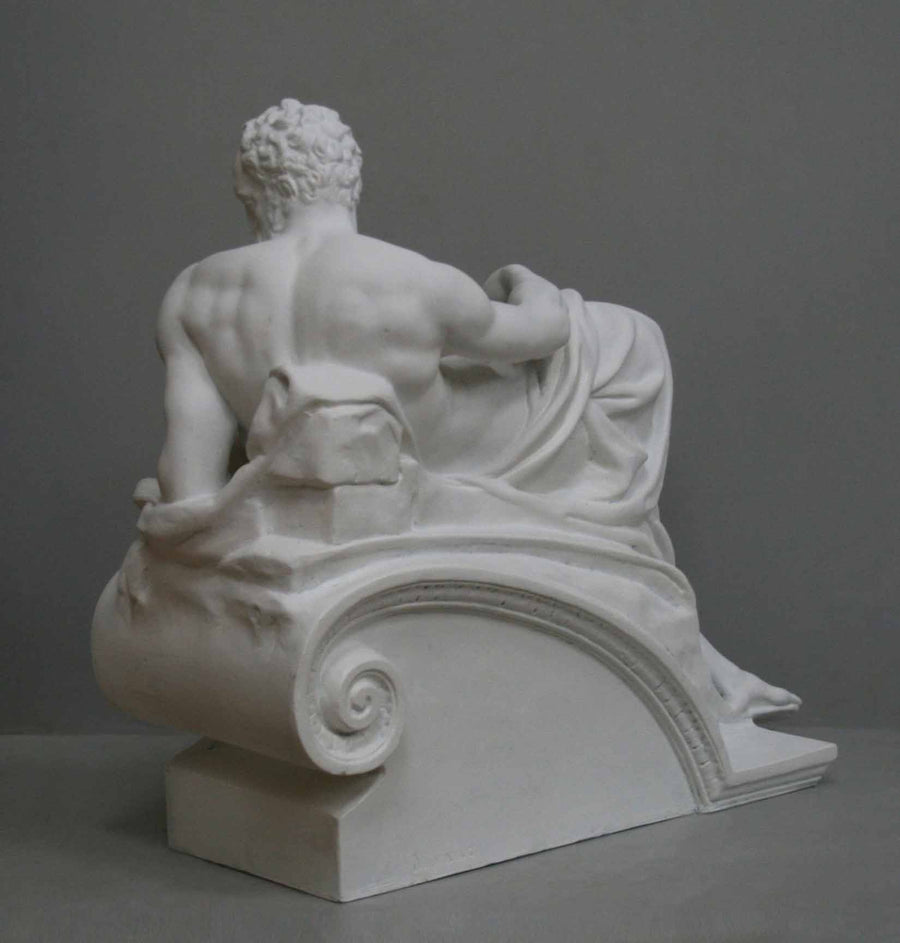 back view photo of plaster cast of reclining male nude with a gray background
