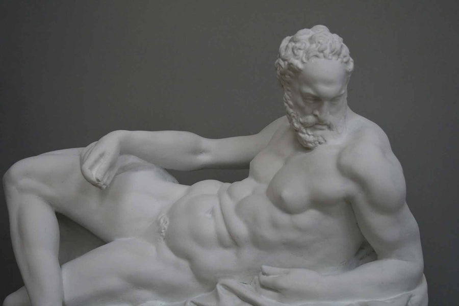photo of plaster cast of reclining male nude with a gray background