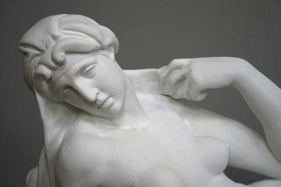 closeup photo of plaster cast of reclining female nude with a gray background