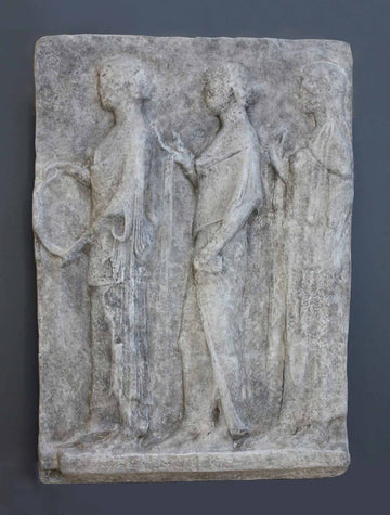 photo of plaster cast sculpture relief with figures walking to the left on gray background