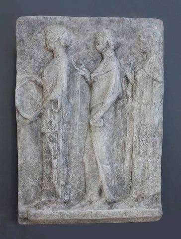 photo of plaster cast of ancient relief with figures on gray background