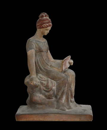 Photo with black background of plaster cast sculpture of female in green-brown tinted robes seated with opened book
