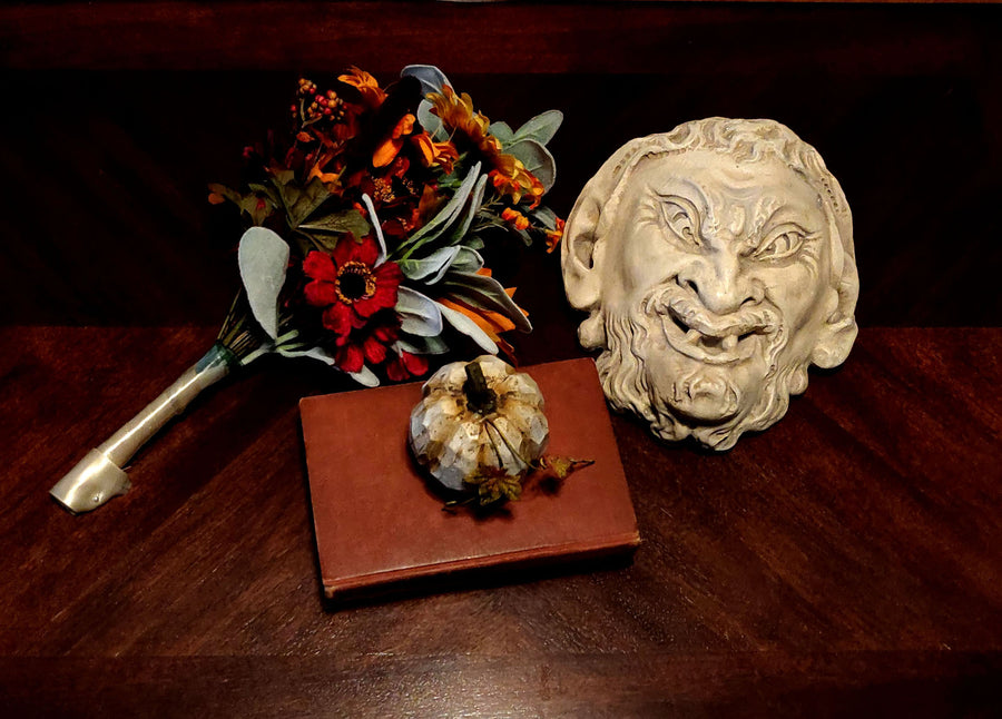 photo of plaster cast sculpture of grotesque faun face on a dark table next to fall flowers, a pumpkin, and a red book