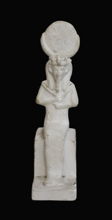 photo with black background of plaster cast sculpture of Egyptian mummy seated