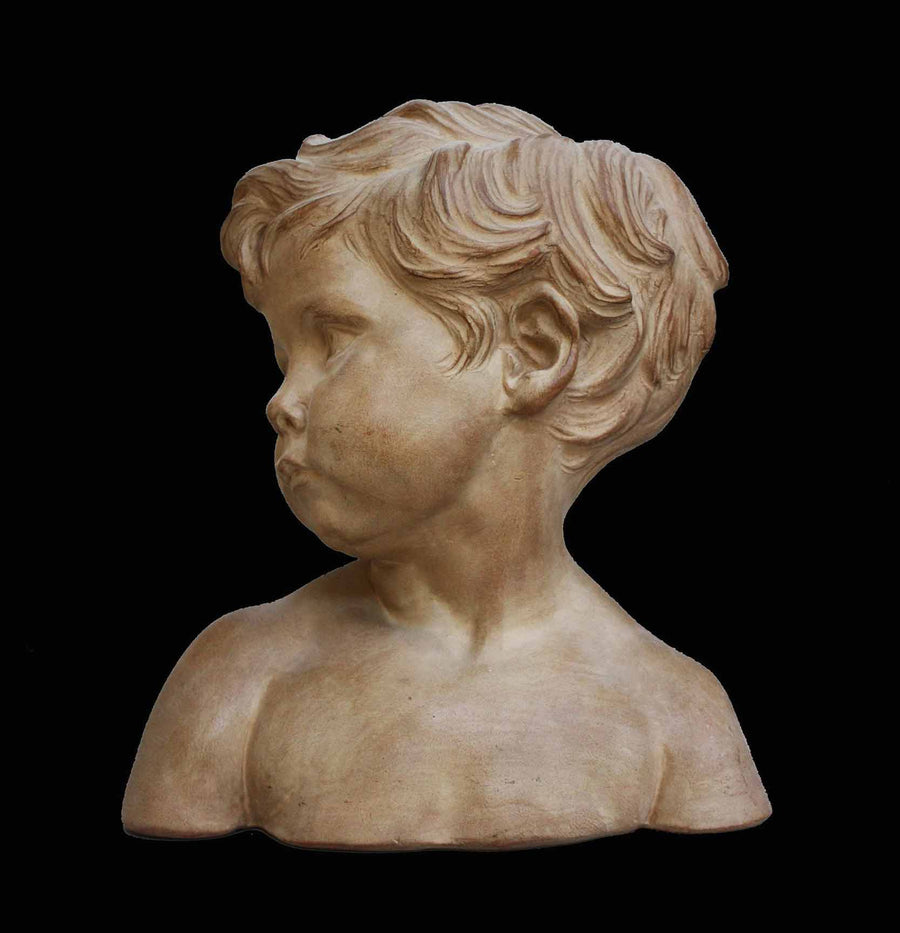 photo of plaster cast bust of boy on a black background