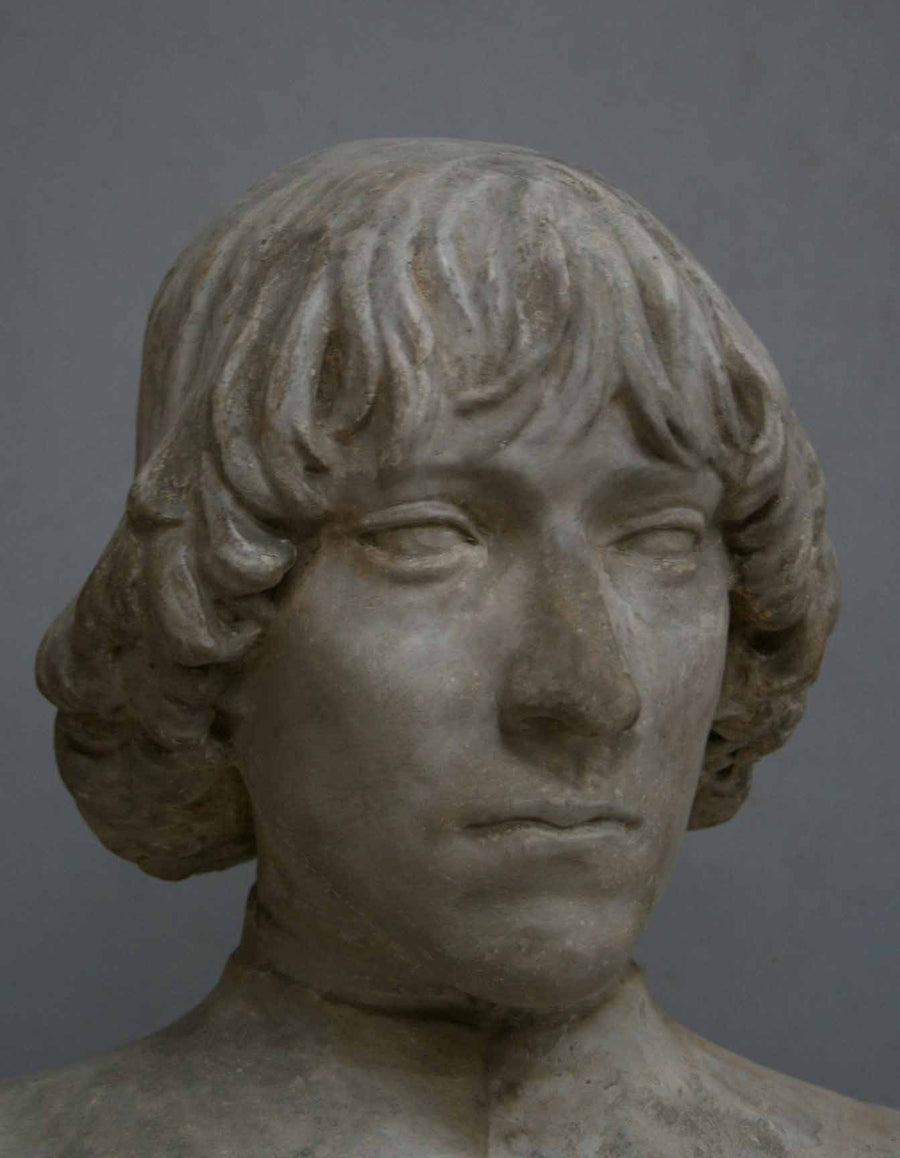closeup photo of plaster cast bust of man with high-neck shirt and shoulder-length hair with gray background