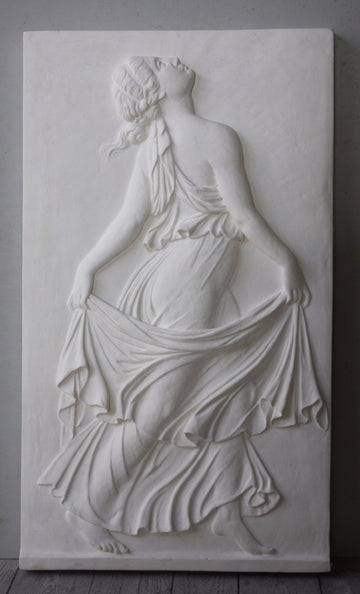 Photo with gray background of plaster cast relief of female in robes dancing and swaying more fabric behind her