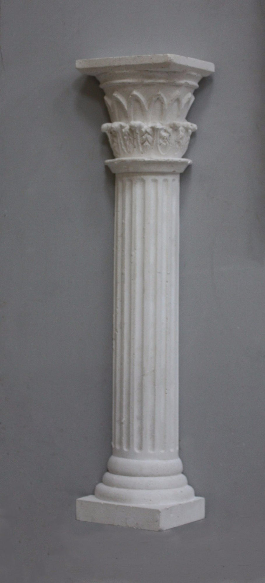 Photo of plaster cast sculpture of Greek half column on a grey background
