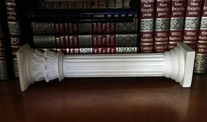 Photo of plaster cast sculpture of Greek half column on a wooden bookshelf with old dictionaries