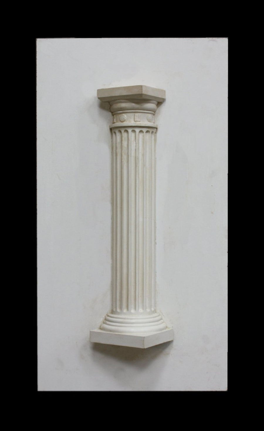 photo of plaster cast sculpture of Greek half column on a white panel
