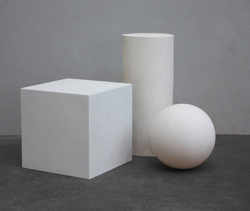 photo with grey background of plaster casts of three shapes arranged in a display- cube, sphere, cylinder