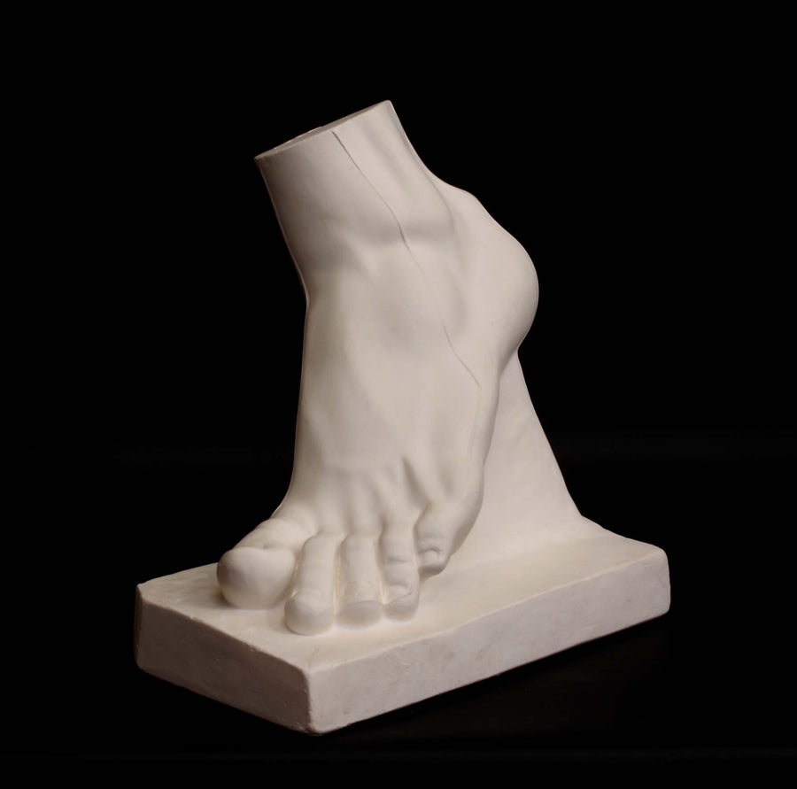 Photo of plaster cast sculpture of foot on a black background