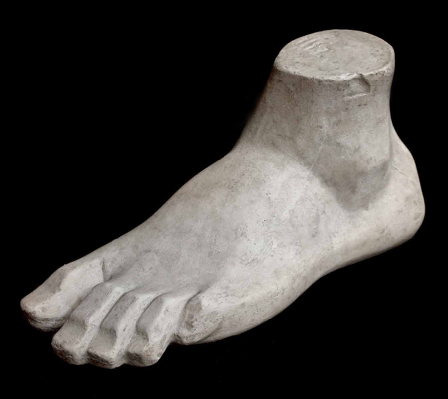 Photo of plaster cast sculpture of blocked foot on a black background