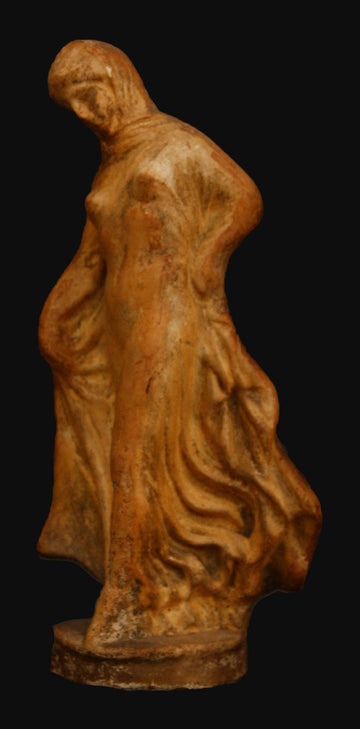 photo with black background of terracotta female dancer in flowing drapery