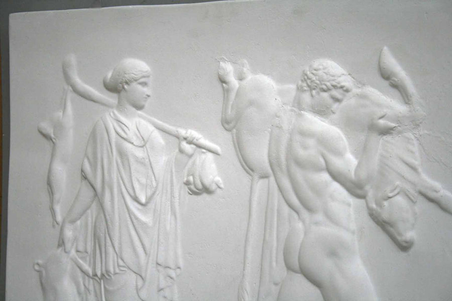 cropped photo of relief plaster cast with two figures walking towards the right