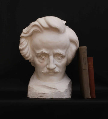 photo of plaster cast sculpture of man's head, namely Edgar Allan Poe, on a base with two books leaning against it on a black background