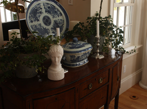 photo of plaster cast of ancient female bust, namely the goddess Diana, on a dark wood table with blue and white china and plants