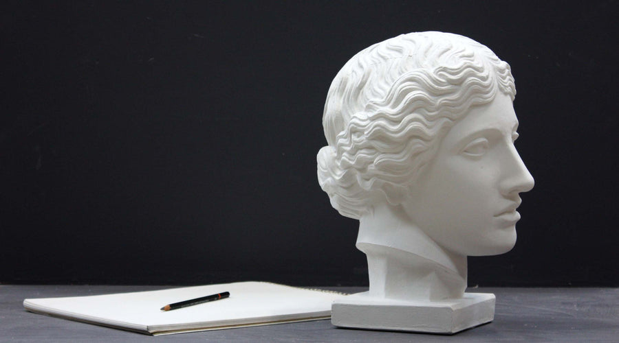 photo of plaster cast of sculpture of an Amazon head- female with pulled-back wavy hair on dark gray surface with sketchbook and pencil beside it