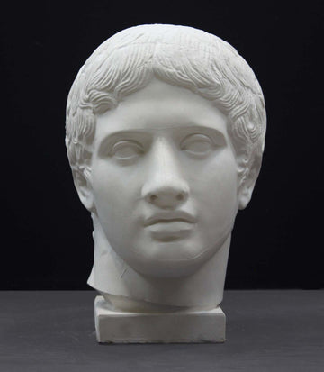photo of plaster cast sculpture of head of the Doryphoros, male with curly hair, on dark gray background