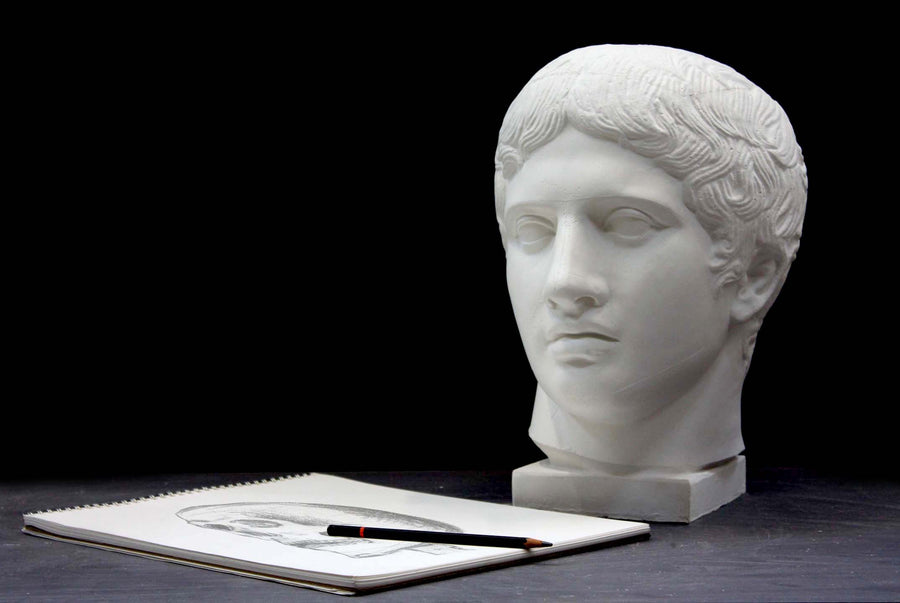 photo of plaster cast sculpture of head of the Doryphoros, male with curly hair, on dark gray surface with sketchbook and pencil beside it