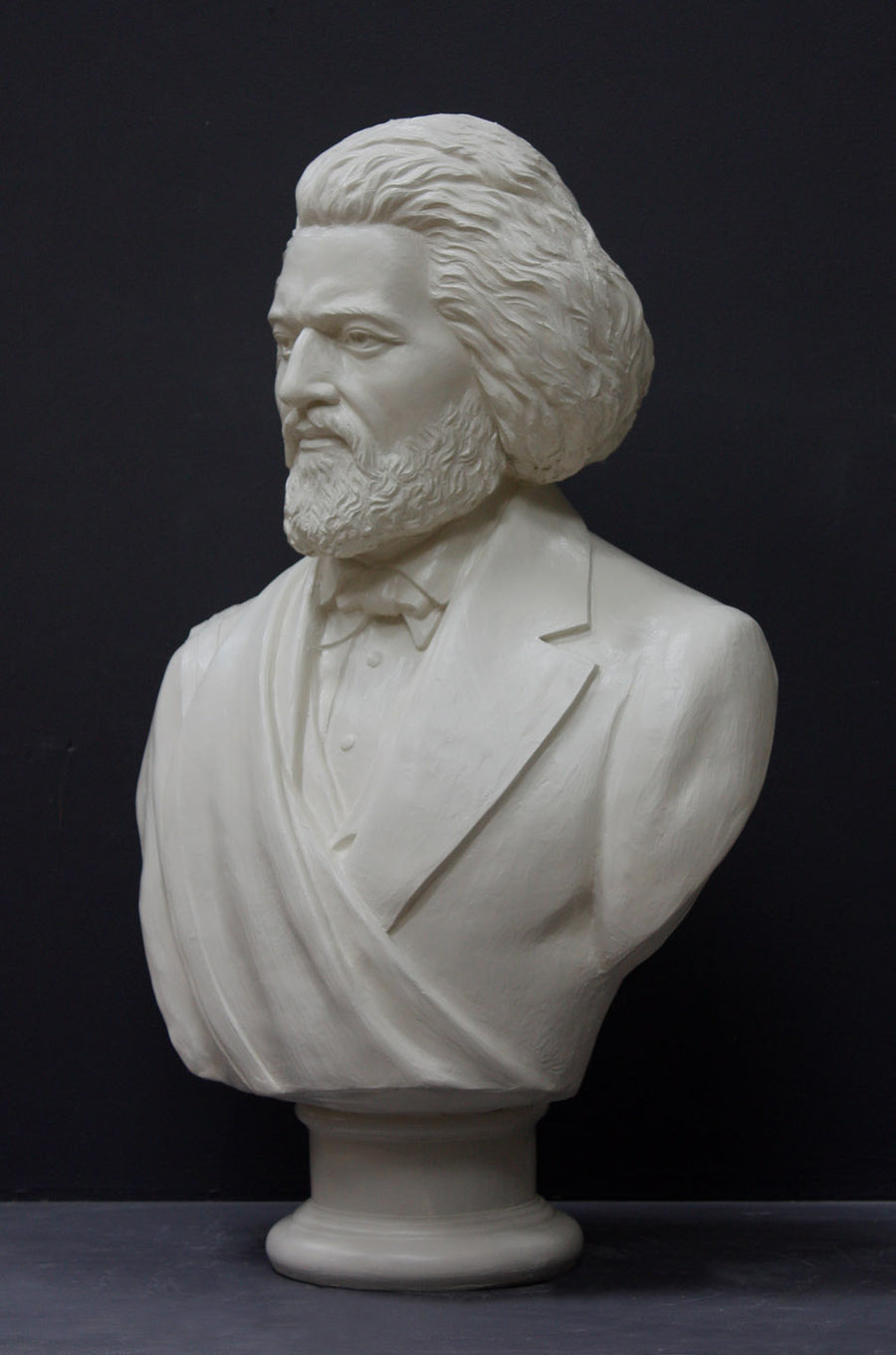 photo of white plaster cast sculpture of bust of Frederick Douglass with beard and in suit coat with toga over one shoulder on dark gray background