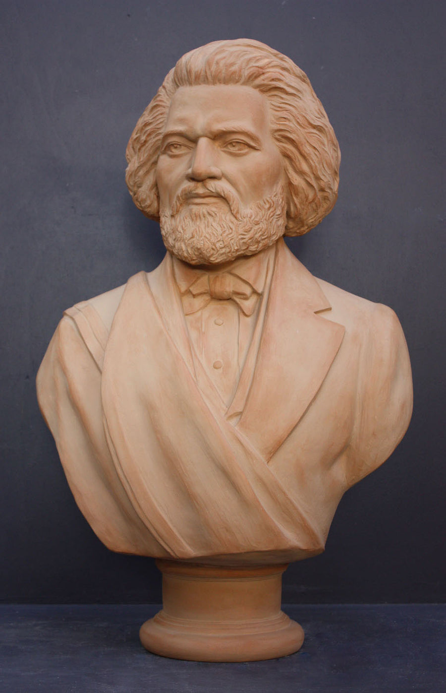 photo of terracotta-colored plaster cast sculpture of bust of Frederick Douglass with beard and in suit coat with toga over one shoulder on dark gray background