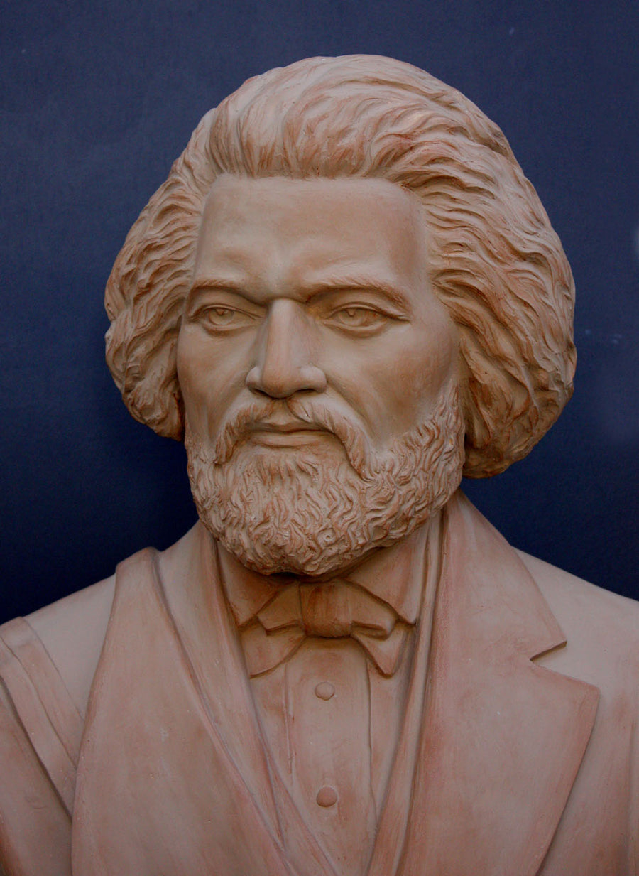 photo detail of terracotta-colored plaster cast sculpture of bust of Frederick Douglass with beard and in suit coat with toga over one shoulder on dark gray background