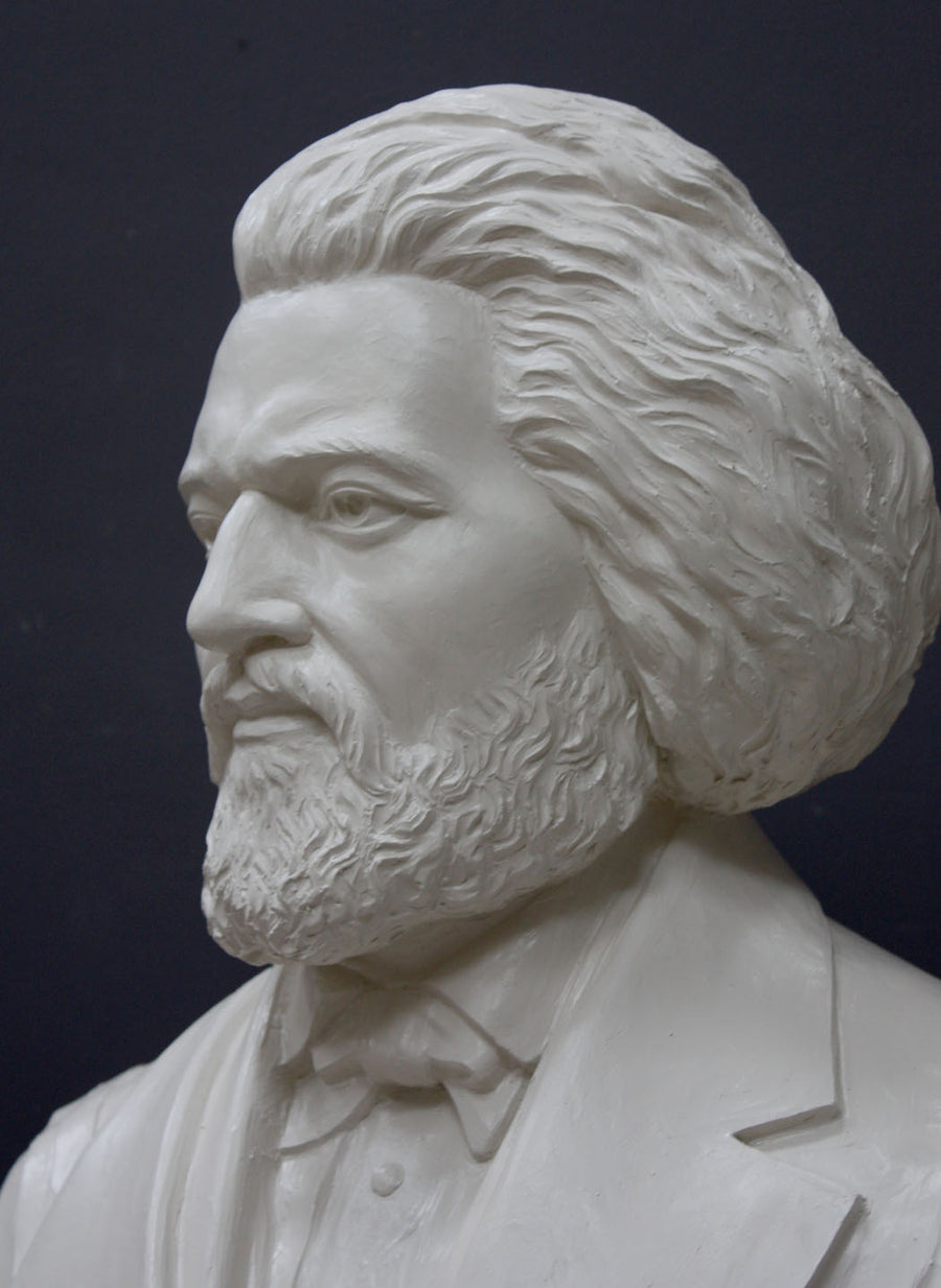 photo detail of white plaster cast sculpture of bust of Frederick Douglass with beard and in suit coat with toga over one shoulder on dark gray background