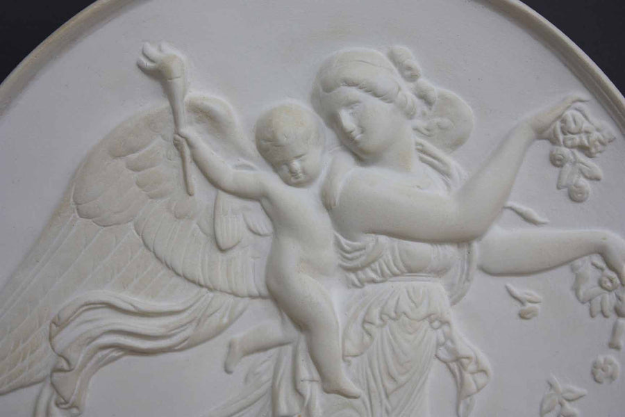 photo with gray background of plaster cast relief of female with wings flying and a cherub on her back