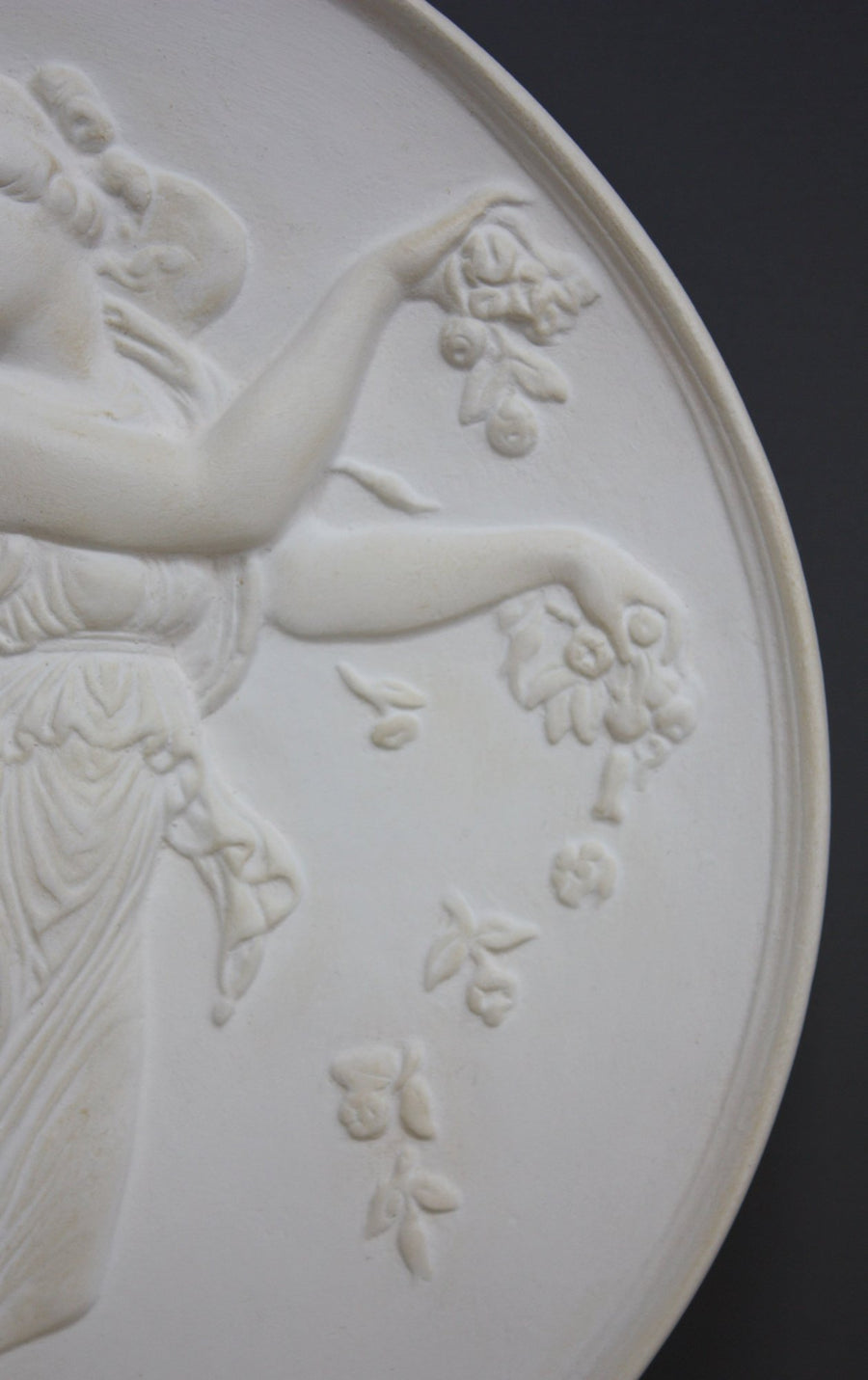photo with gray background of plaster cast relief of female with wings, closeup of arms
