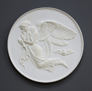 photo of plaster cast relief of woman with wings flying with two children nestled against her and an owl flying on a dark background