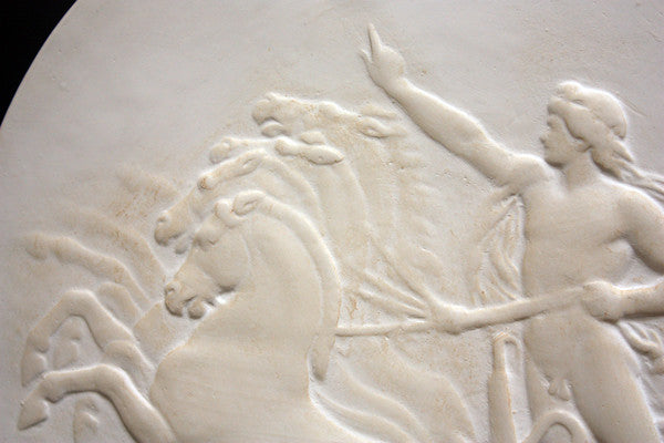 closeup photo of plaster cast relief sculpture of nude male figure in horse-drawn chariot flying