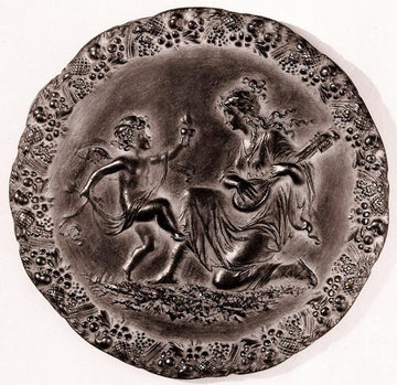 photo with tan background of bronze-colored plaster cast relief sculpture of a child dancing and a female figure playing an instrument