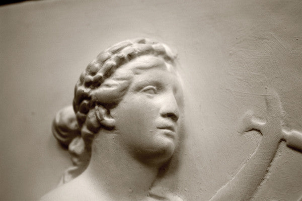 photo closeup of plaster cast sculpture relief of man's head, namely the god Apollo