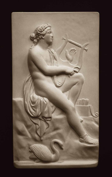 photo with black background of plaster cast sculpture relief of man, namely the god Apollo, seated on rock and playing a lyre
