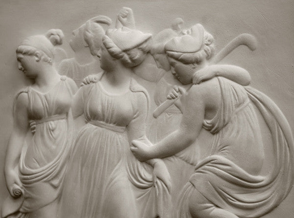 Photo with black background of plaster cast sculpture relief of females dancing