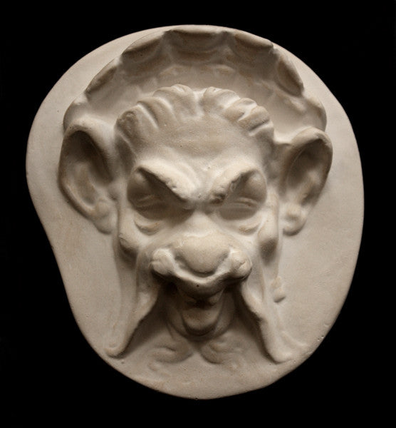 Photo of plaster sculpture of a Faun Head on a black background