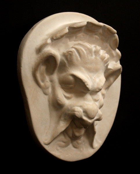 Photo of the side of a plaster sculpture of a Faun Head on a black background