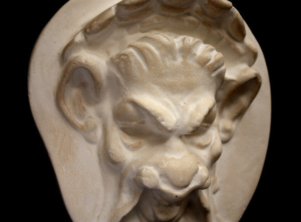 Photo of a cropped plaster sculpture of a Faun Head on a black background
