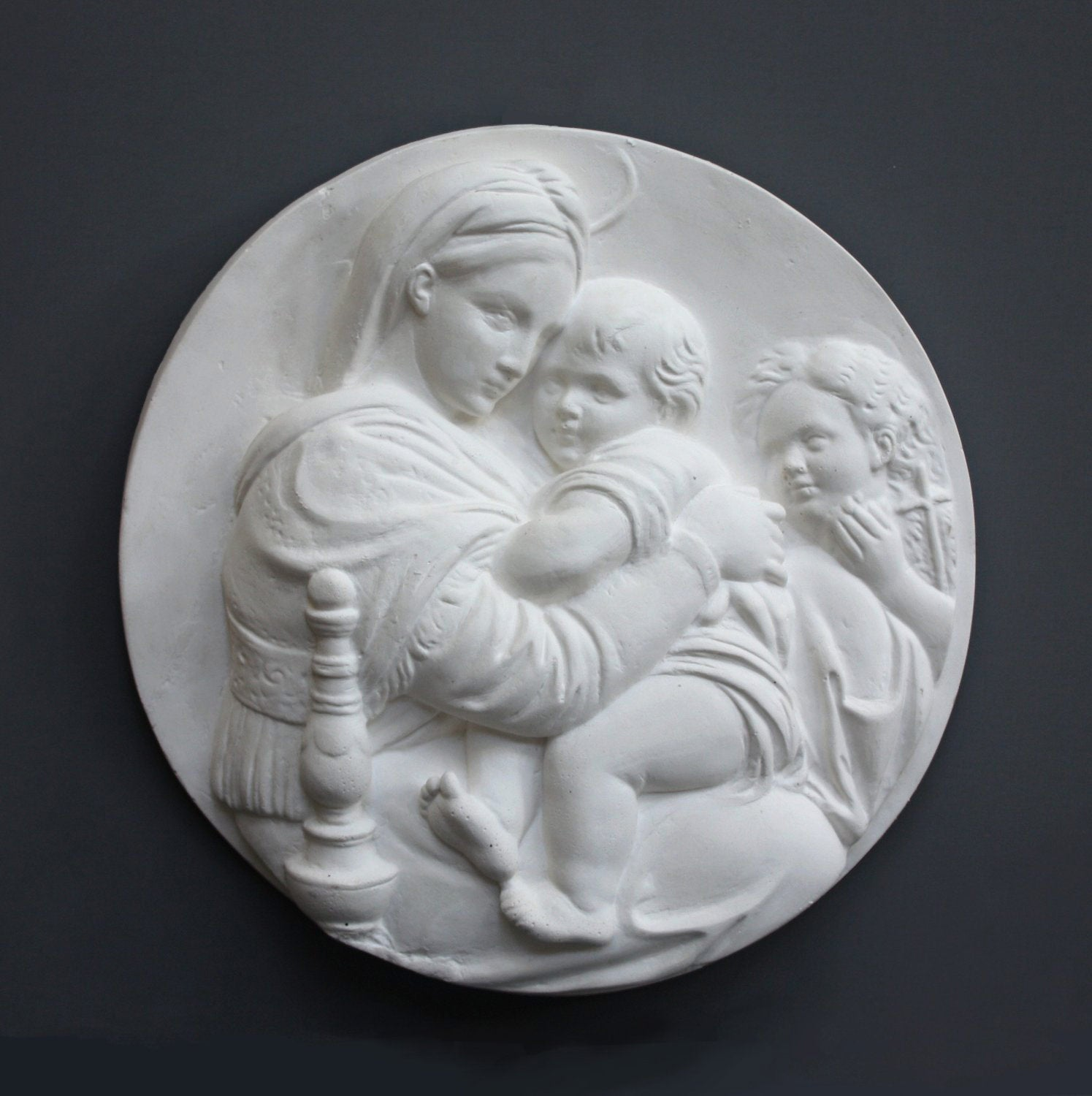 photo of relief plaster cast featuring the Madonna, Child, and St. John and hanging on a dark-colored wall