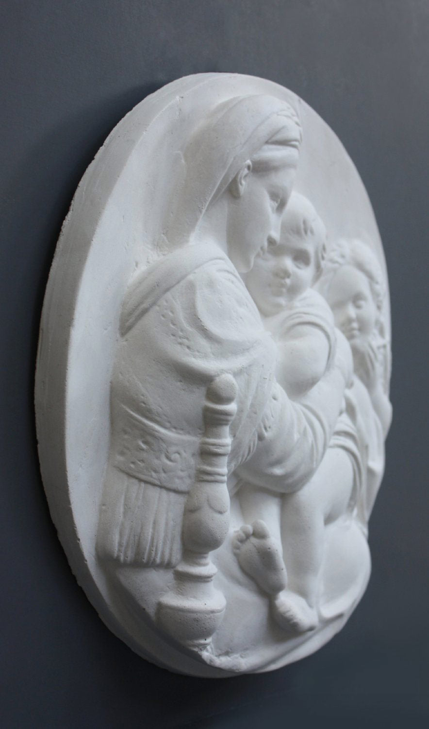three-quarter photo of relief plaster cast featuring the Madonna, Child, and St. John and hanging on a dark-colored wall