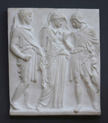 photo with gray background of plaster cast of ancient relief with three figures