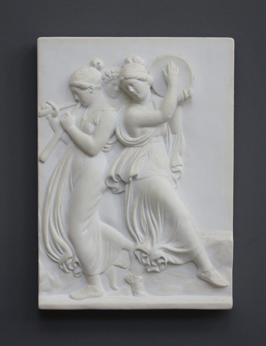 Photo with black background of plaster cast sculpture relief of females playing instruments