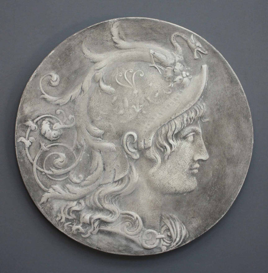 photo of relief plaster cast with profile portrait of the goddess Minerva hanging on a gray-colored wall