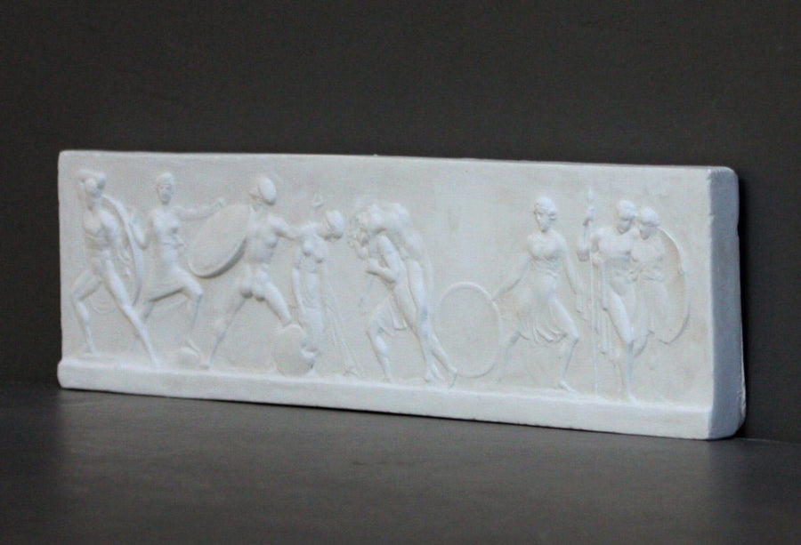 photo with gray background of plaster cast of small ancient relief sculpture with figures
