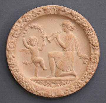 photo with gray background of plaster cast of small relief with a dancing child and a young man playing two horns