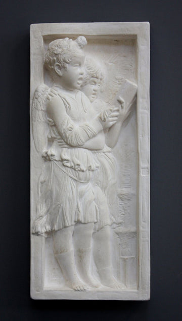 photo with gray background of plaster cast sculpture of relief with two angels singing from a book