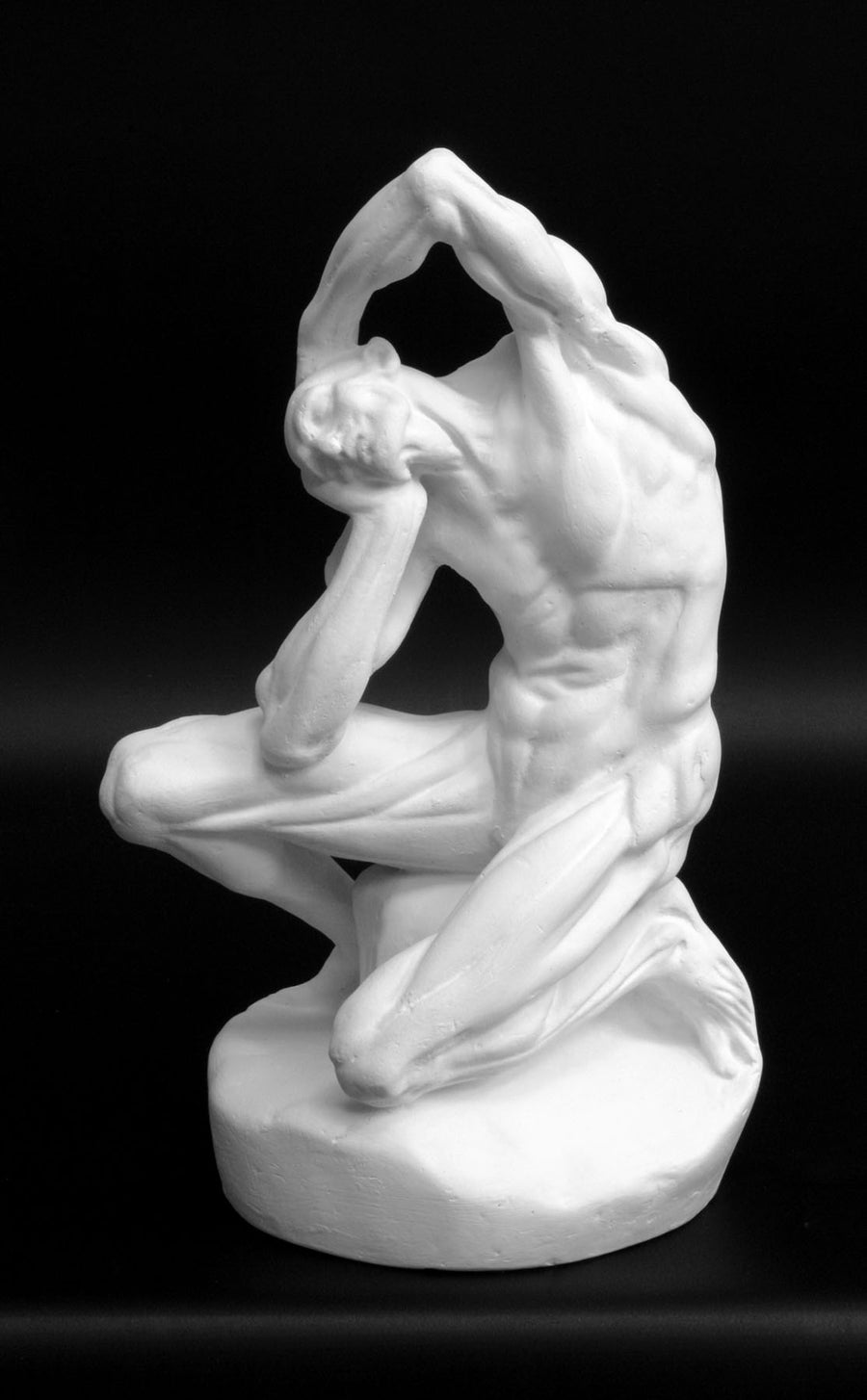Photo of plaster cast sculpture of flayed man kneeling with hands on head on black background