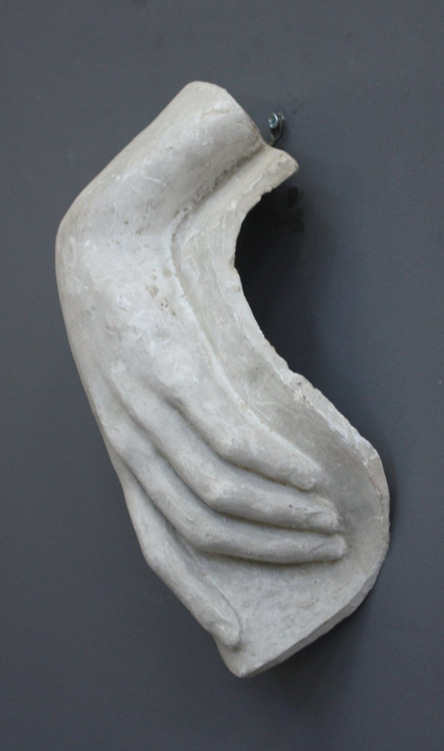 photo with gray background of plaster cast sculpture of female left hand on a curved panel with fingers curled except index finger that points