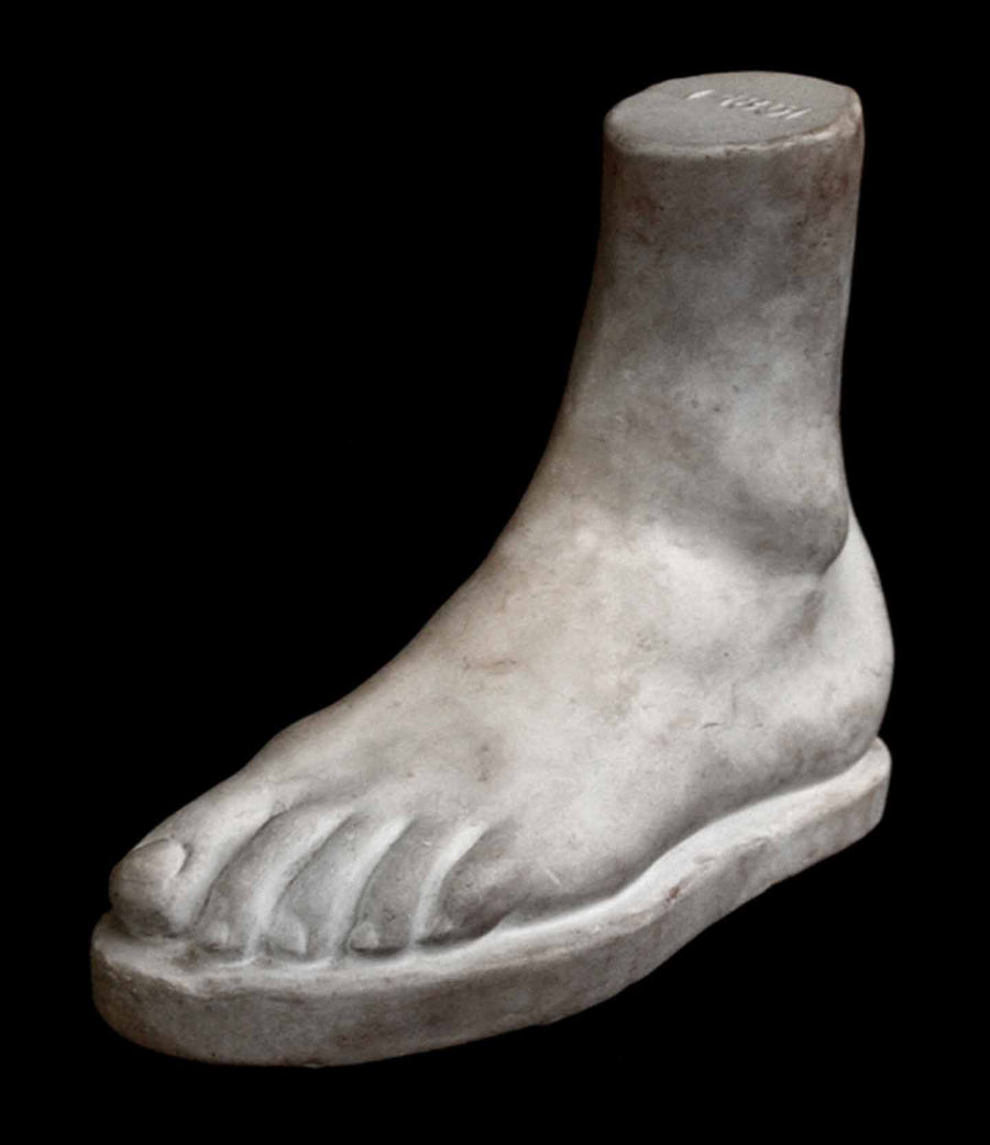 Photo of plaster cast male foot sculpture on a black background
